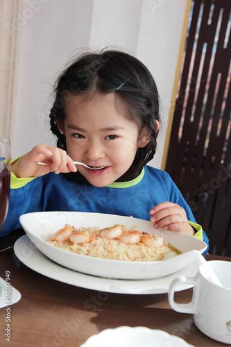 Foto op Canvas Kruidenierswinkel ピラフを食べる少女