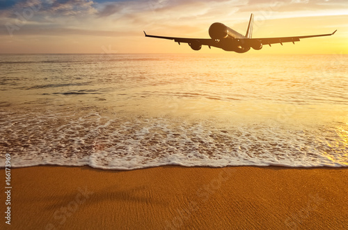 Staande foto Oceanië Airplane flying over tropical beach with smooth wave and sunset sky abstract background.