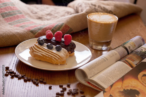 Cappuccino, cake with berries and a journa on table. Tableau sur Toile