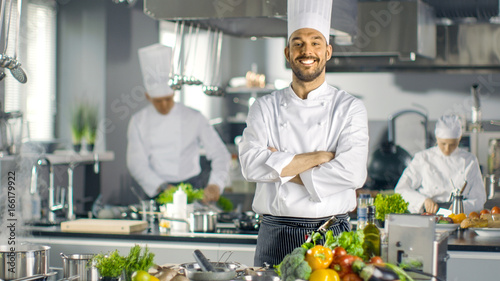 Photo Stands Cooking Famous Chef of a Big Restaurant Crosses Arms and Smiles in a Modern Kitchen. His Staff in Working in the Background.