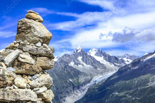 Foto auf Gartenposter Reflexion cairn in the foreground and alps range