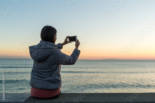 Valokuva  Woman taking photon with seascape and sunset