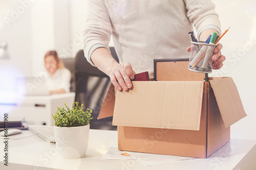Sad dismissed worker taking his office supplies with him Fototapeta