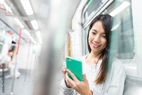 Photo  Woman using cellphone on train
