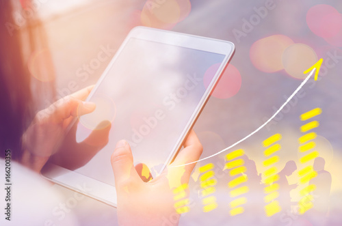 Business economic and technology working concept. Woman using smart phone on street double exposure graph money stock trading up trend arrow bar bokeh background.