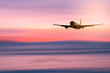 Airplane flying over blur tropical beach with smooth wave and sunset sky abstract background.