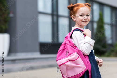 cute little redhead schoolgirl in eyeglasses holding backpack and smiling at cam Canvas Print