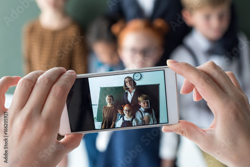 Fototapeta close-up view of young female teacher and cute little students photographing with smartphone obraz na płótnie