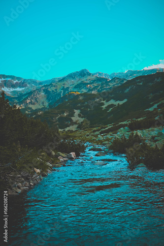 Beautiful view on the high green mountains peaks and a mountain river, blue sky background. Mountain hiking paradise landscape, A stream flows down the rocks, no people.