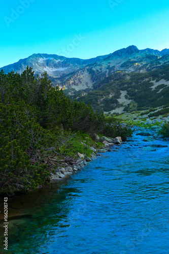 Keuken foto achterwand Turkoois Beautiful view on the high green mountains peaks and a mountain river, blue sky background. Mountain hiking paradise landscape, A stream flows down the rocks, no people.