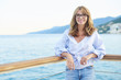 Enjoy my vacation. Portrait of an attractive middle aged woman standing outdoor in the background with the sea.