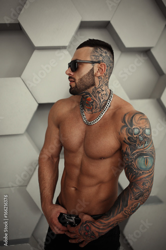 Foto  Sexy closeup topless portrait of Elegant handsome male model with fashion tattoo and a black beard standing and posing for tests or to journal in trend fashionable clothes