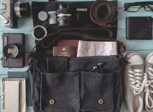 Fototapeta koncepcja podróży, strój podróżnika z filmu retro aparat, torba vintage, notatnik, paszport, okulary, tenisówka, pasek, smartphone na drewniane tła, styl vintage ton