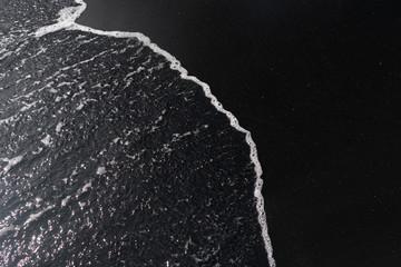 white ocean foam on black sand volcanic texture