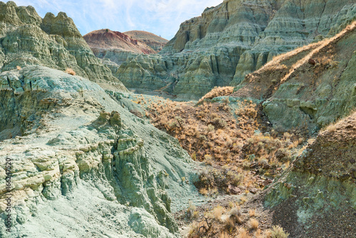 Poster Kaki Surrealistic landscape in John Day Fossil Beds National Monument Blue Basin area with grey-blue badlands. A branched ravine and Heavily eroded formations.
