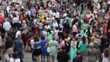 Blurred Background - The Crowd, A Large Number of People Dressed in Bright Holiday Clothes Go to Different Parties. Summer Sunny Weather.
