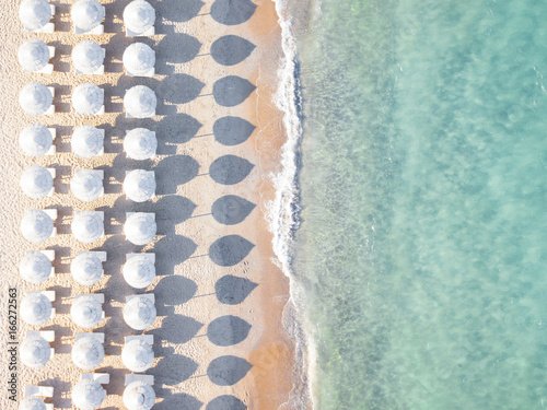 View from above, stunning aerial view of an amazing empty white beach with white beach umbrellas and turquoise clear water during the sunset. Mediterranean sea, Sardinia, Italy.