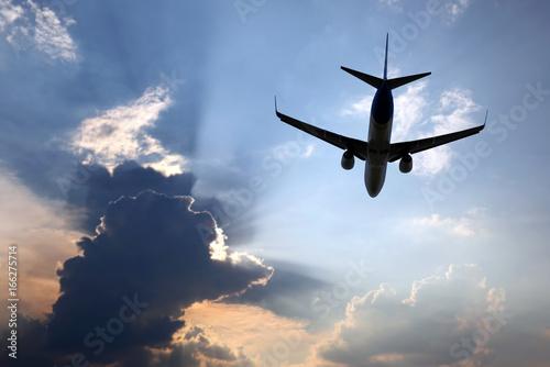 Plakat samolot pasażerski leci w soczystych chmurach, aby spotkać słońce.