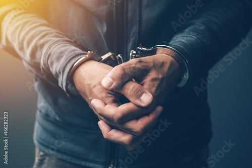 Canvas Arrested computer hacker with handcuffs