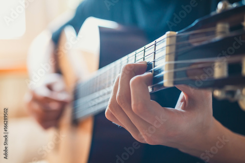 Leinwand Poster young musician playing acoustic guitar, live music background