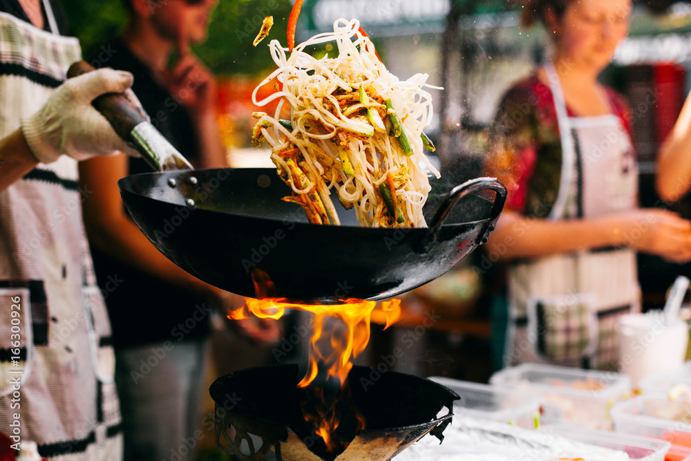 Fototapety, obrazy: Man cooks noodles on the fire