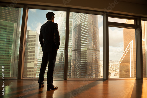 Leinwand Poster Thoughtful contemplative businessman wearing suit standing back holding hands in