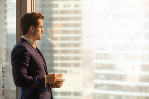 Valokuva  Side view of serious pensive director of prosperous company enjoying cup of coff