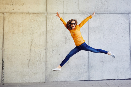 Fotografia Joyful young lady jumping and raising arms in front of wall outside