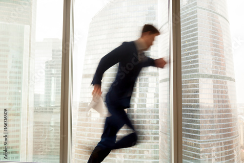 Cuadros en Lienzo Busy businessman hurrying up to come at meeting on time in office building, blur