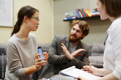 Portrait of young Asian woman accusing her husband of adultery showing text mess Wallpaper Mural
