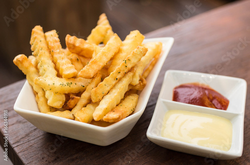 Deurstickers Klaar gerecht French fried in white bowl with tomato sauce and mayonnaise on wooden table