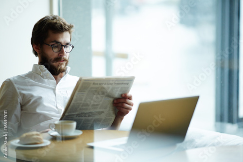Fotografie, Obraz  Seerious man reading vacancy adverts in newspaper