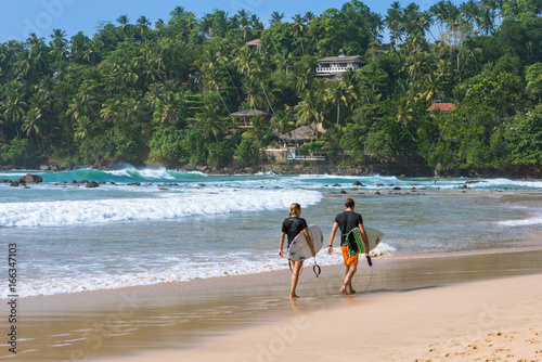 The beach and bay of Mirissa. Surfer with their boards on the way to the waves. The beach at the south coast is very popular among surfer. It is a top spot for aquatic sports