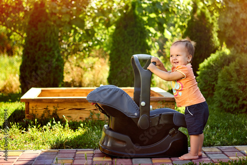 Infant baby standing near modern car seat in a park Poster
