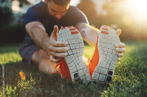 Fotografia, Obraz Attractive young man stretching in the park before running at the sunset focus o