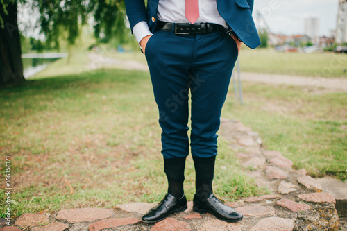 Valokuvatapetti Unrecognizable man in wedding suit standing outdoor with socks put on trousers