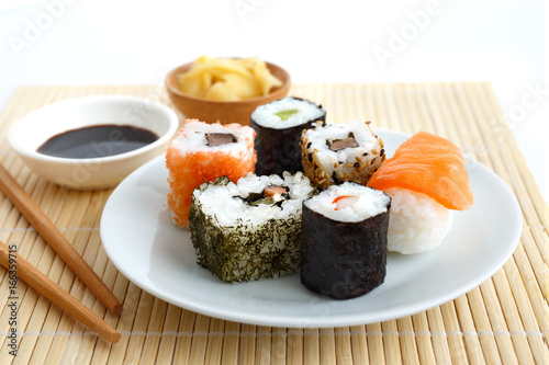 Foto  Selection of sushi on bamboo mat with chopsticks, soya sauce and pickled ginger