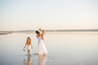 Happy Mom with two beautiful little girls walking in white dresses on the lake