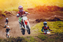 Young Child Racer On A Motorcycle Participates In Motocross Cross-country In Flight, Jumps And Takes Off On A Springboard On The Team Of Rivals. Concept Active Extreme Rest.