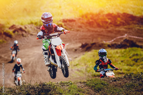 Obraz na plátně  Young child racer on a motorcycle participates in motocross cross-country in flight, jumps and takes off on a springboard on the team of rivals