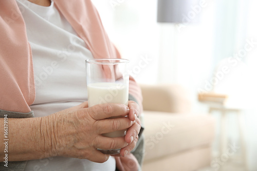 Old woman holding glass with fresh milk, closeup