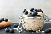 Jar Of Overnight Oats With Fresh Blueberries And Bananas, Scene With White And Black Stone Background