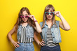 canvas print picture - Portrait of two young woman with sunglasses on yellow background
