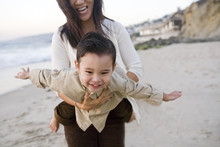 Mother Holding Son In Flying Position