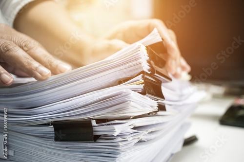 Fototapeta Businessman working on stack reports papers files on desk work in office, business paperwork or piles of unfinished documents achieves with paperclip on offices in Business obraz