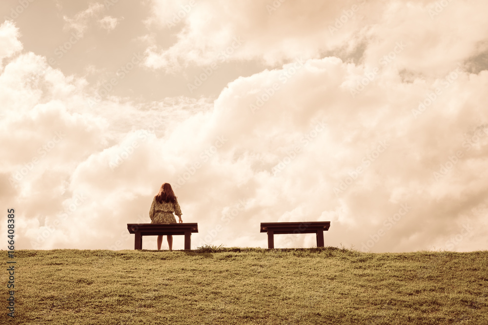 Fototapeta a women sitting alone on a bench waiting for love, alone concept