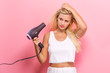 canvas print picture - Beautiful woman holding a hairdryer on a pink background