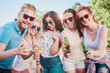Friends posing at outdoor party while standing and drinking alcohol