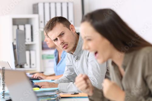 Fotografia Jealous employee looking at a successful colleague