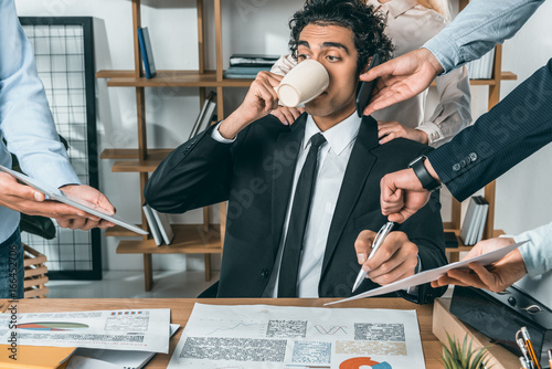 Fotomural portrait of busy businessman drinking coffee and sitting at workplace while coll